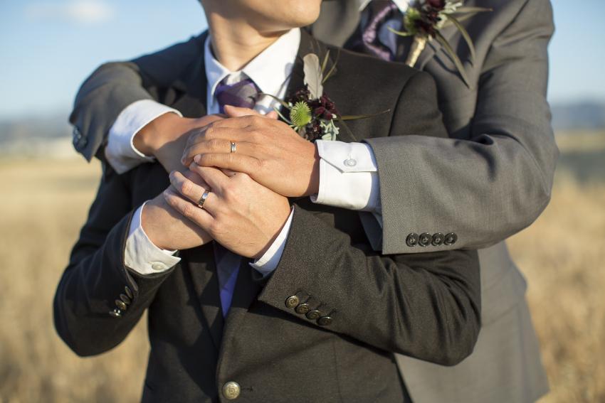 2 Männer umarmen sich und präsentieren ihre Eheringe