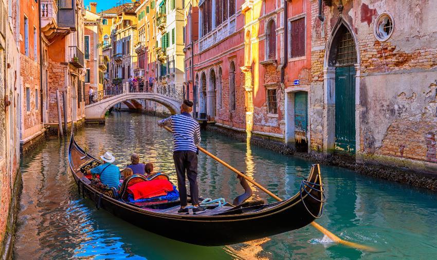 Gondoliere fährt einige Touristen durch einen Kanal Venedigs