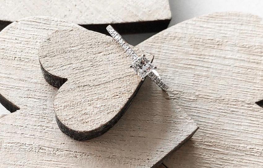 Ein Verlobungsring liegend auf einem Herz aus Holz