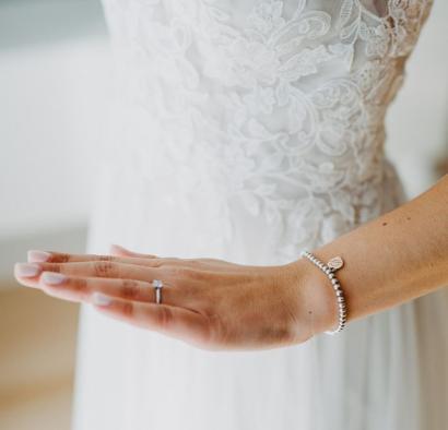 Braut zeigt Hand mit Verlobungsring