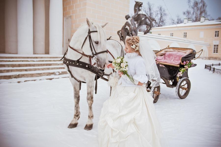 Braut mit weissem Pferd im Schnee der-ideale-hochzeitsmonat
