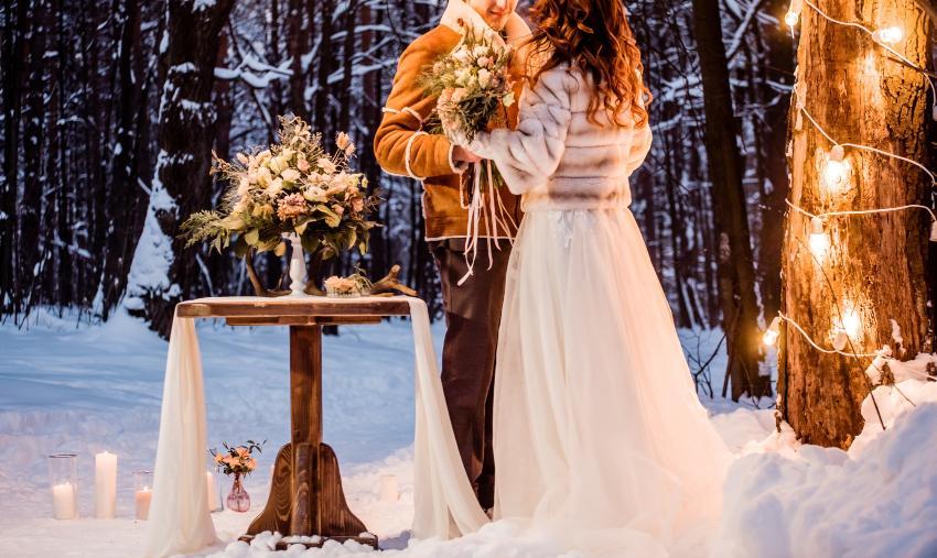 Brautpaar im Schnee mit Kerzenlicht und Beleuchtung - romantische Winterhochzeit