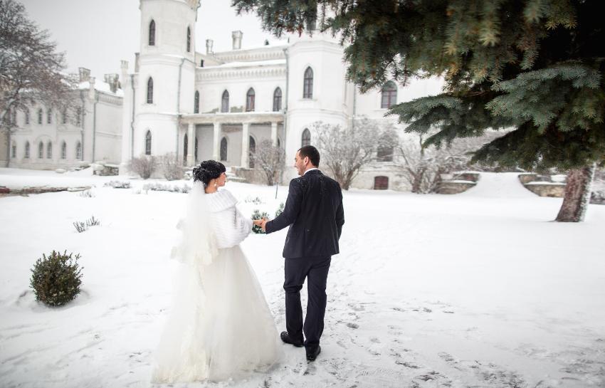 Hochzeitspaar läuft im Schnee Richtung Schloss