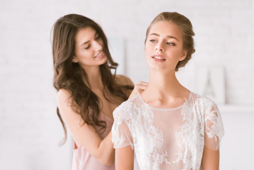 Brautjungfer hilft der Braut bei den Ankleide - eine der vielen Aufgaben einer Brautjungfer