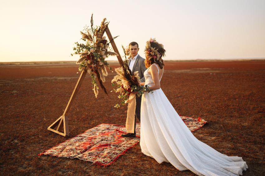 Junges Ehepaar auf einem abgelegenen Feld mit Picknickdecken