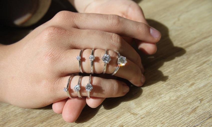 Hand mit diversen Verlobungsringen - Juwelier auf einer Hochzeitsmesse