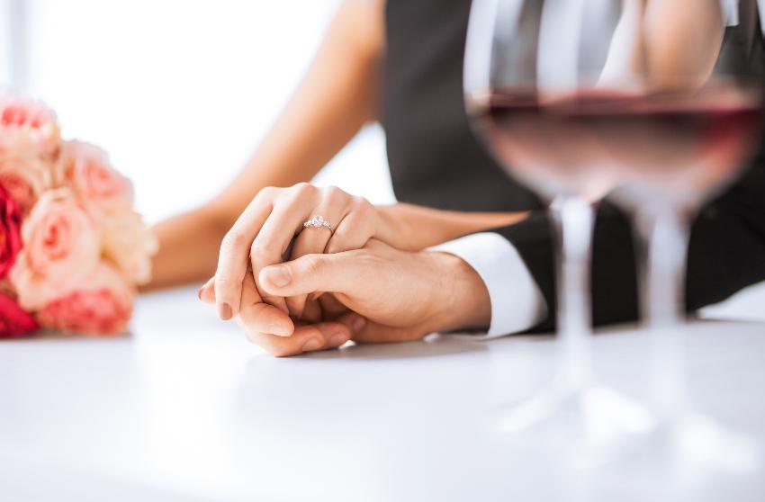 Verlobtes Paar mit Ringen und Weingläsern