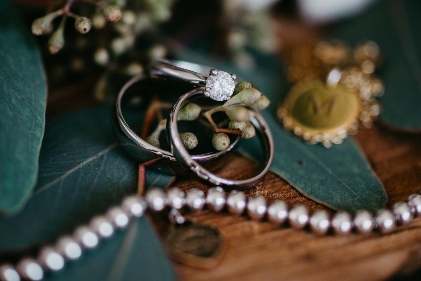 Verlobungsringe mit Diamant vor einem Blätterhintergrund
