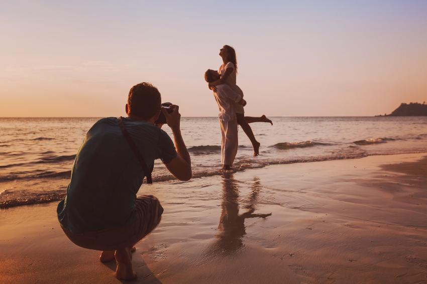 Frau und Mann am Strand werden fotografiert