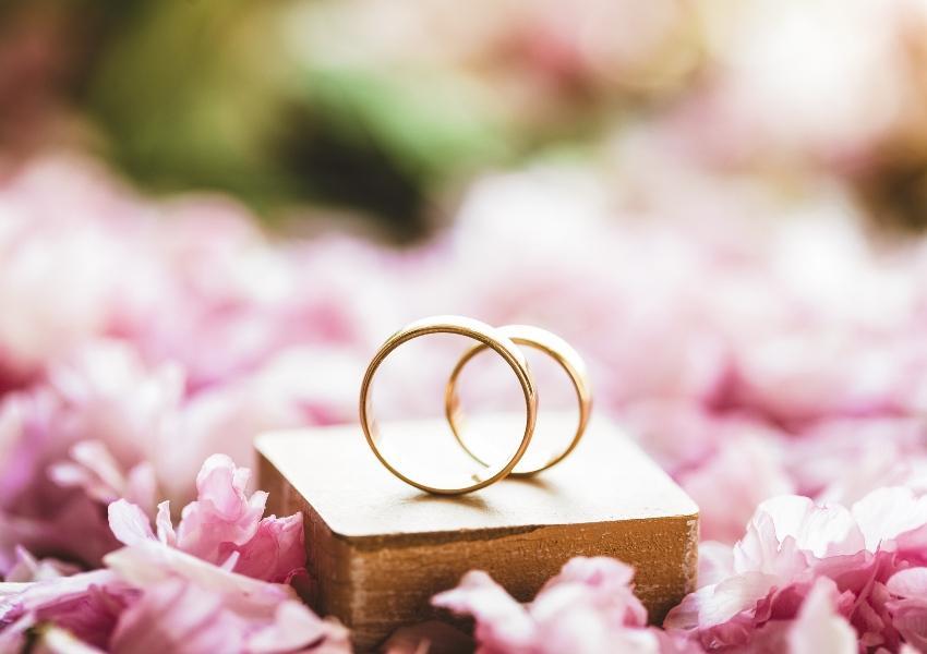 Goldene Eheringe mit Blumen geschmückt