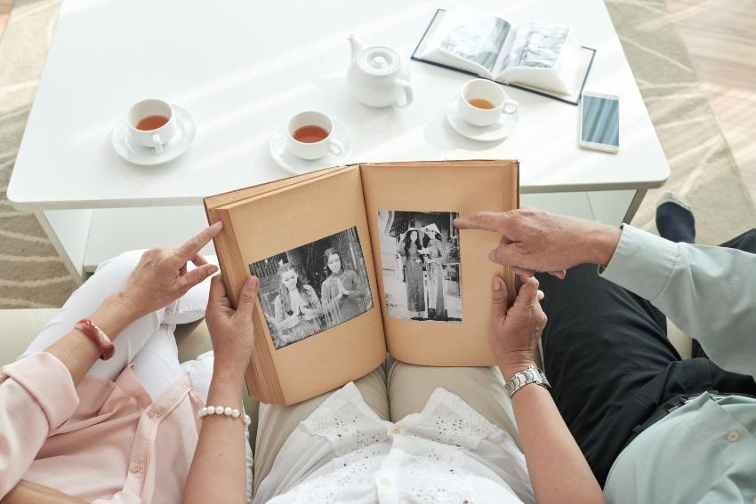 Altes Paar schaut in ein Fotoalbum - Goldene Hochzeit Geschenk