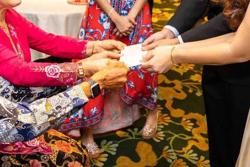 Älteres Paar übergibt dem Hochzeitspaar einen Umschlag