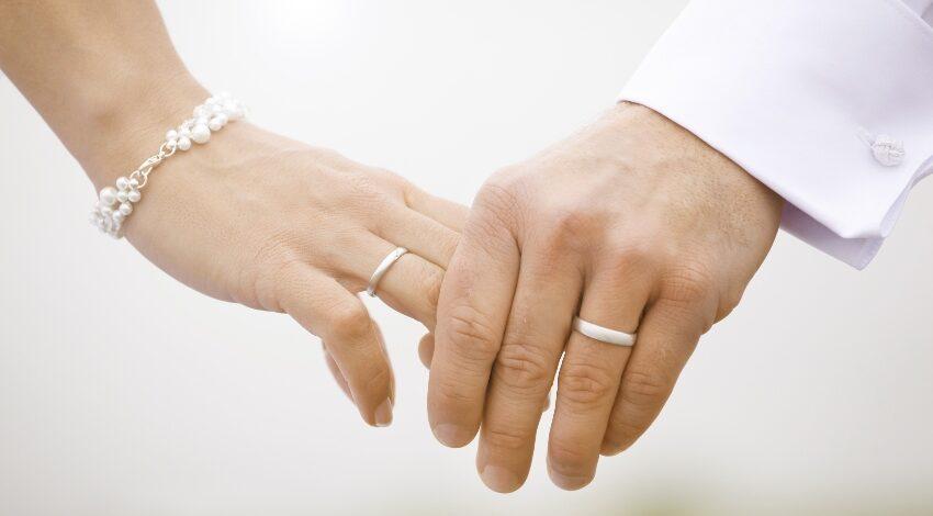 Hochzeitspaar hält sich bei den Händen
