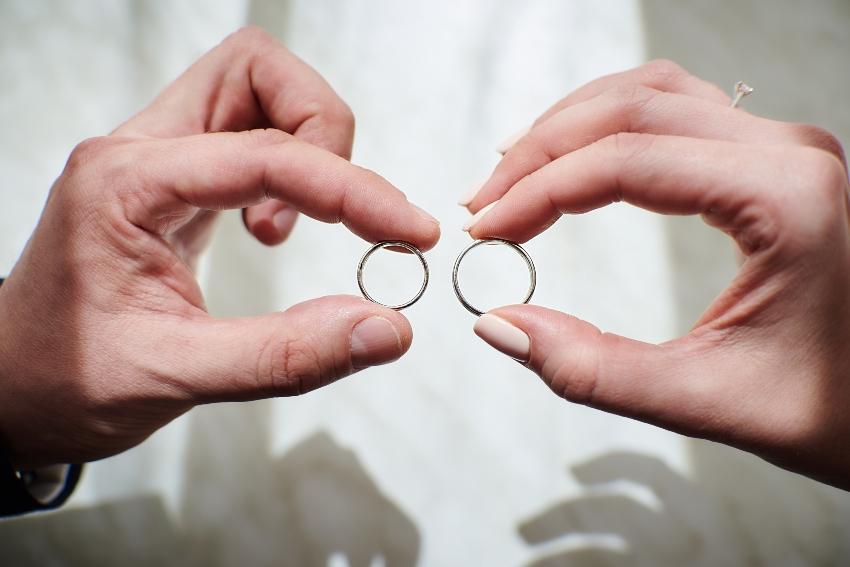 Zwei Hände, die je einen Ring halten - Verlobungsring-Sets