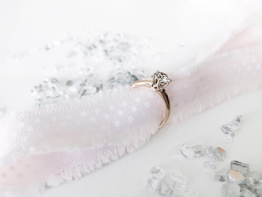 Verlobungsring mit einem Geschenkband drapiert