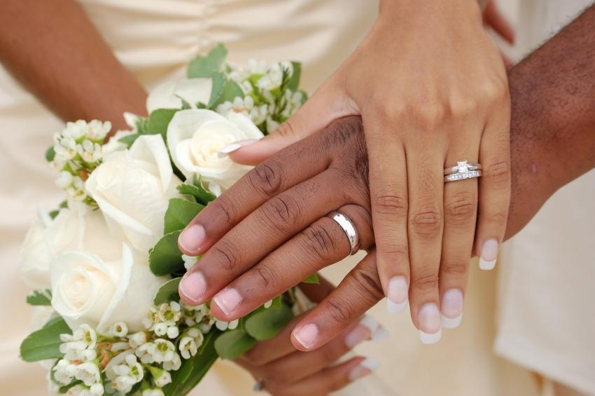 Verheiratetes Paar hält sich die Hände mit den Ringen