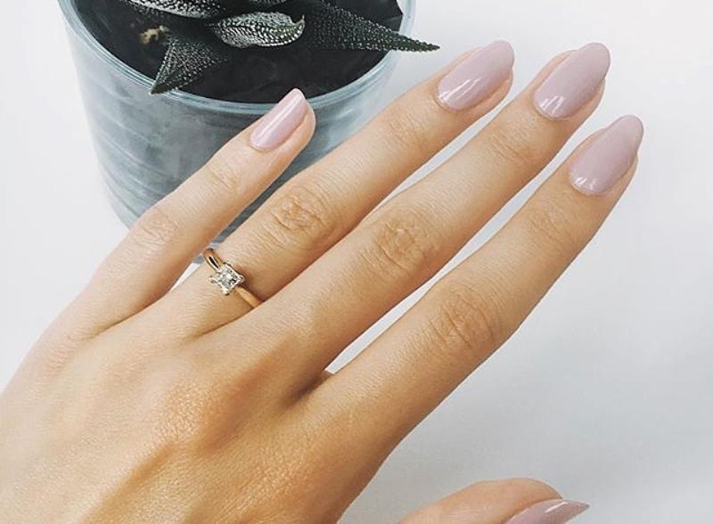 Eine filigrane Damenhand, die einen herrlichen Diamantring am Finger trägt