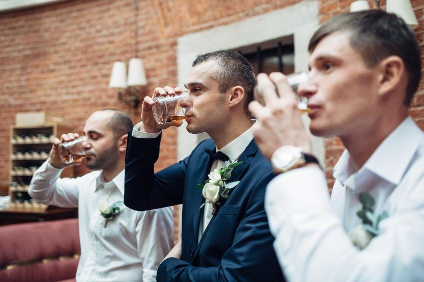 Männer in einer Reihe trinken Whisky aus einem Glas - schottische Hochzeit