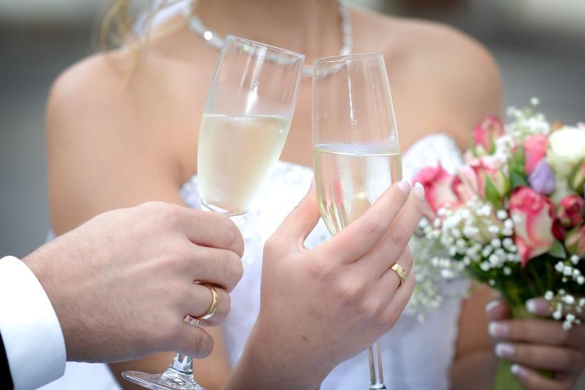 Braut und Bräutigam mit Sekt in der Hand