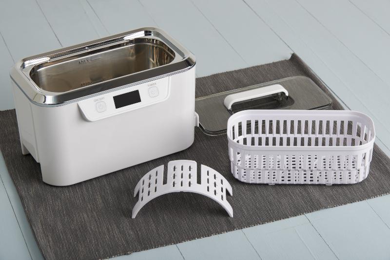 Einzelne Bestandteile eines Ultraschall-Reinigungsgeräte: Korb, Deckel und Wanne