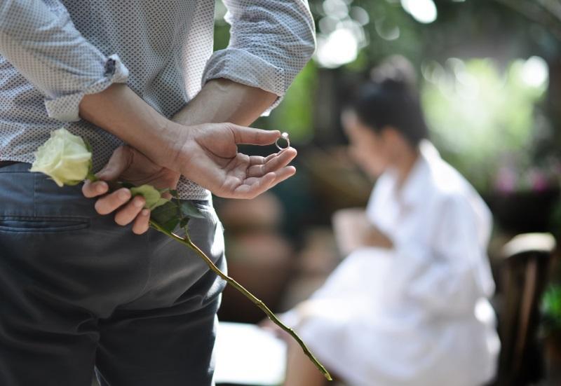 Ein Mann hält hinter seinem Rücken eine Rose und einen wunderschönen Verlobungsring. Im Hintergrund sieht man seine Angebetete, die noch nicht ahnt, dass er ihr gleich einen Antrag machen wird.