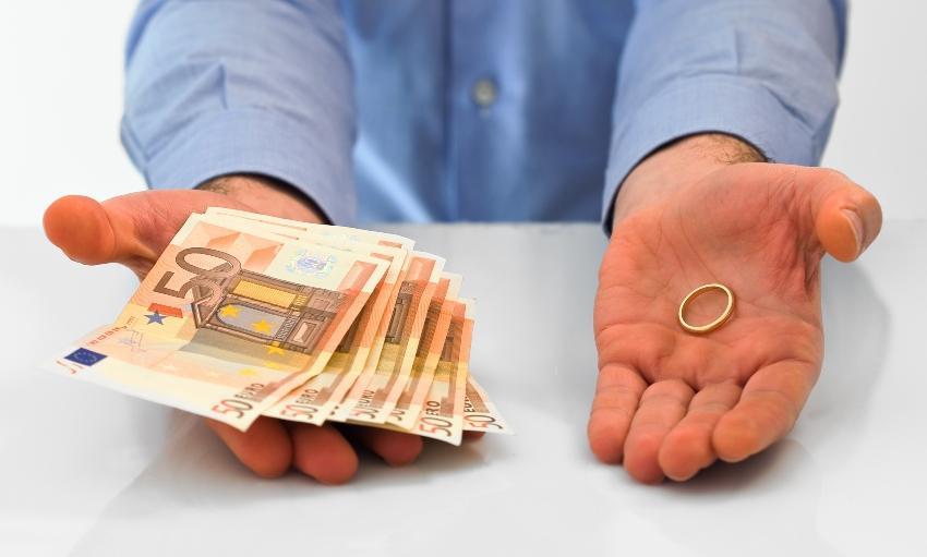 Mann mit Geldscheinen in der einen und Ring in der anderen Hand
