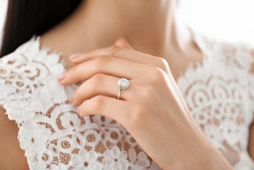 Frau trägt Verlobungsring mit großem Diamanten