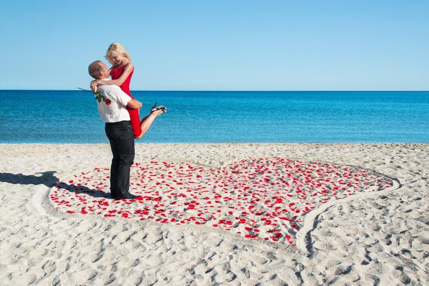 Paar am Strand mit einem Herz aus Rosen