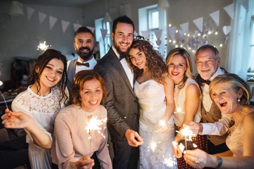 Brautpaar umgeben von Familienmitgliedern, die Wunderkerzen halten - Heiraten trotz Corona