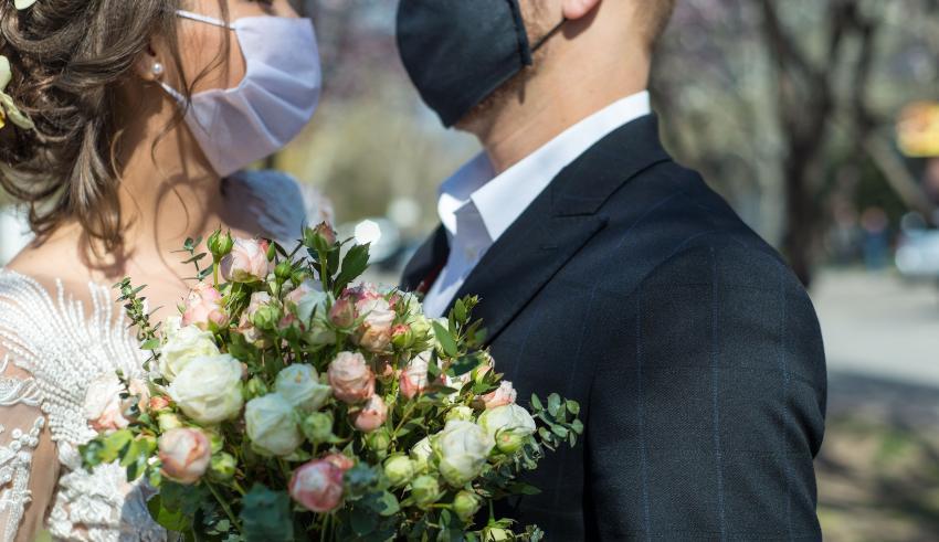 Brautpaar blickt sich an - beide tragen Mundschutz