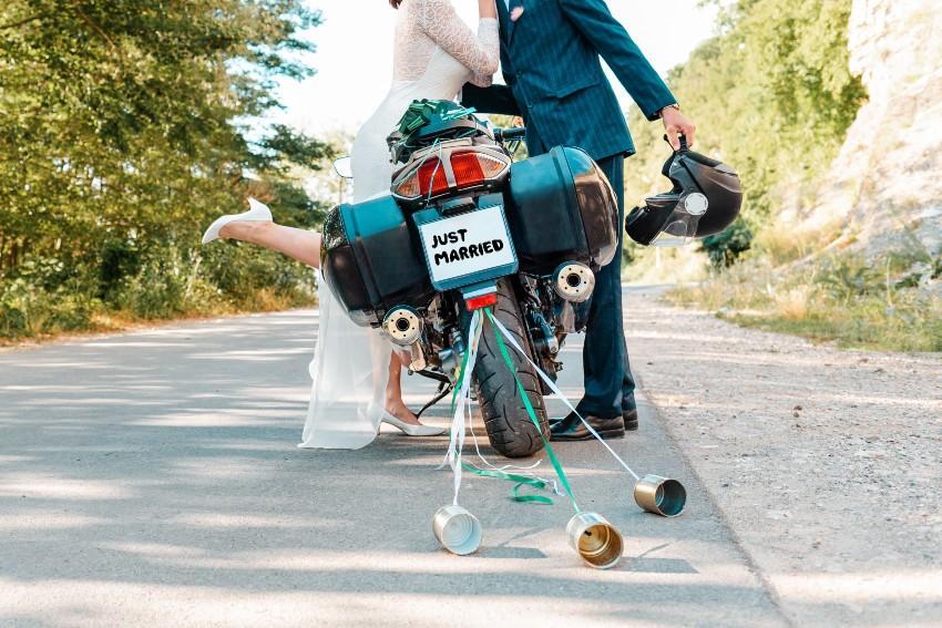 """Hochzeitspaar vor dem Motorrad mit """"Just Married"""" Schild"""
