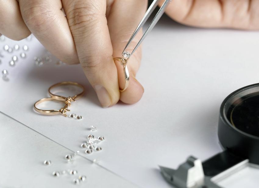 Goldschmied beim Einsetzen von Diamanten - Weißgold