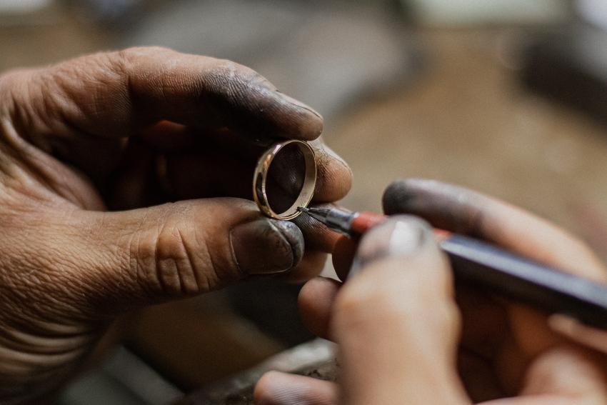 Hände gravieren einen Verlobungsring für Männer