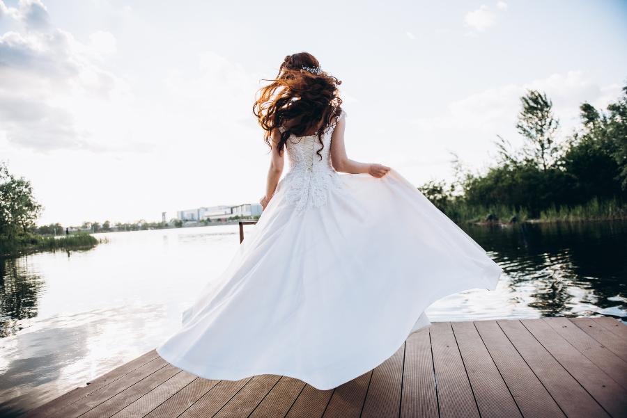 Braut in einem schoenen Hochzeitskleid auf einer Holzbruecke am See