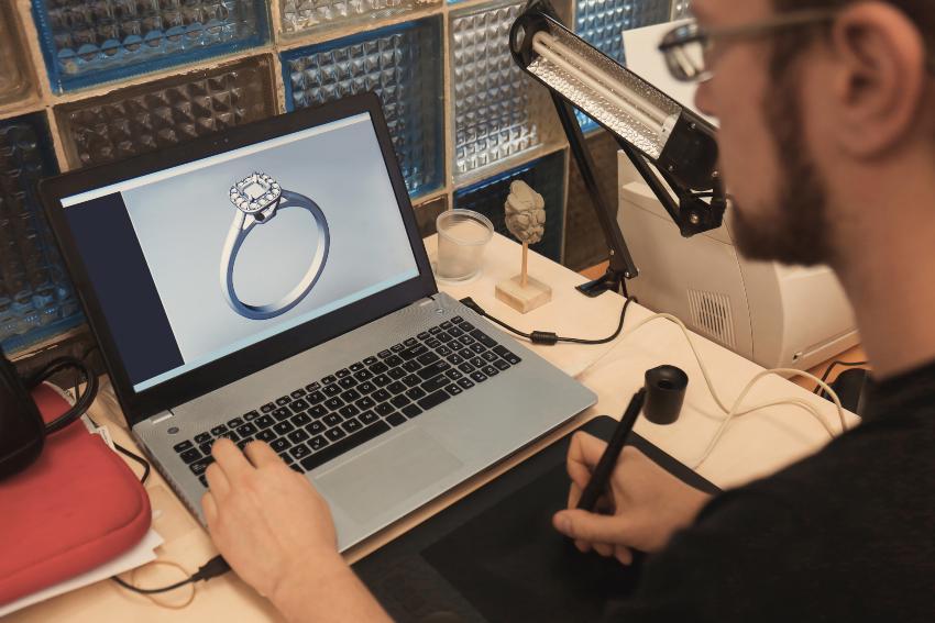 Mann designt Ring am Computer