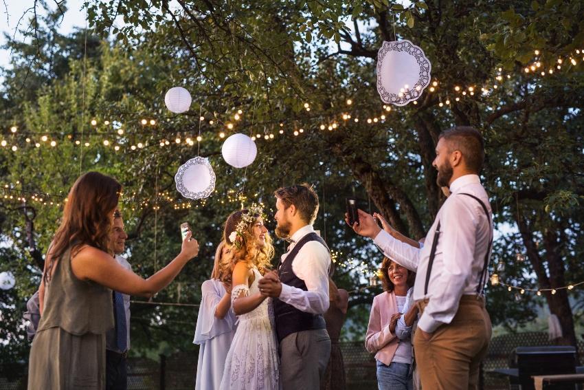 Junges Ehepaar feiert im Garten mit Freunden