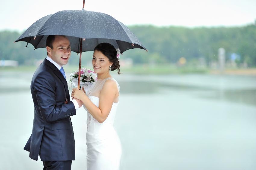 Frischvermählte stehen unter einem Regenschirm
