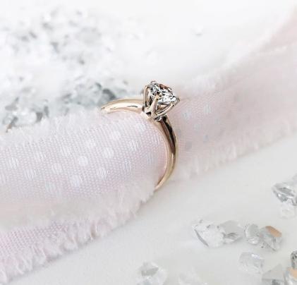 Verlobungsring mit Diamant auf Stoff drapiert