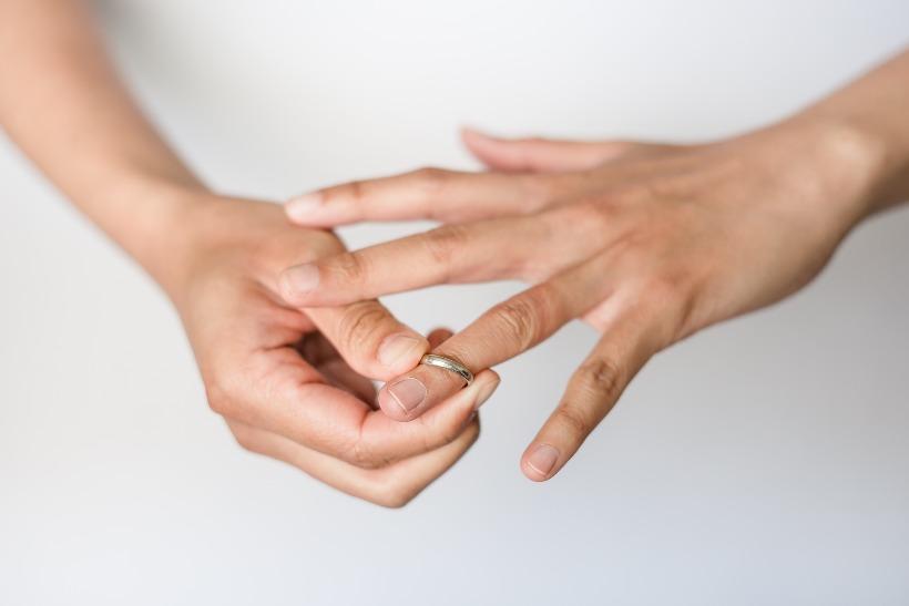 Frau nimmt Ehering ab
