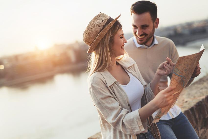 Junges Paar mit Stadtplan steht an einem Fluß