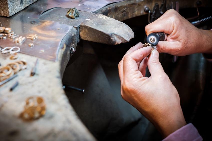 Juwelier poliert Ring mit Maschine