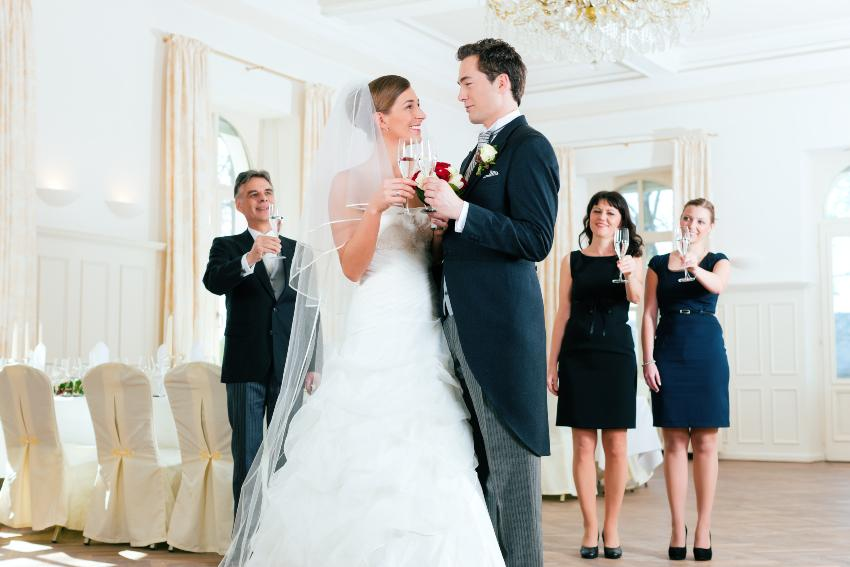Hochzeitspaar stößt in kleinem Kreis an - Micro Wedding