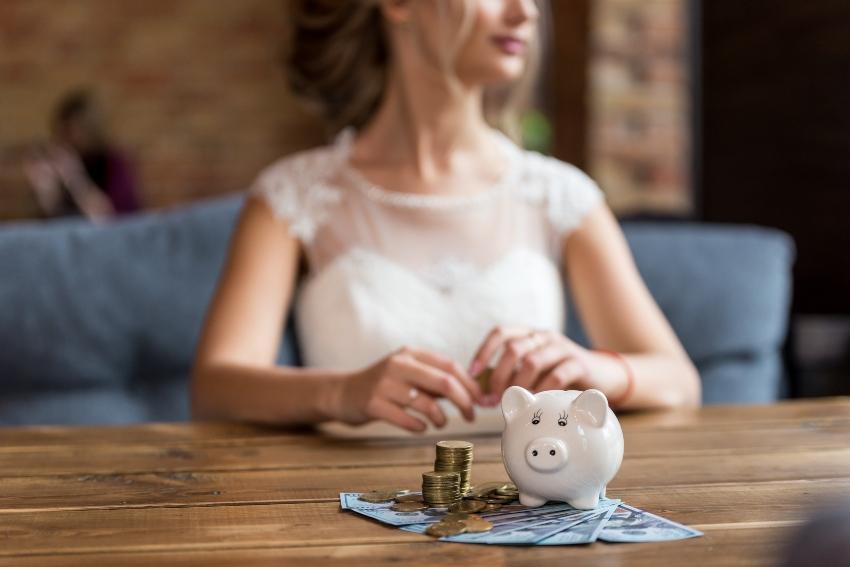 Junge Braut sitzt vor Sparschwein - ein Weddingplaner kann durchaus Kosten sparen