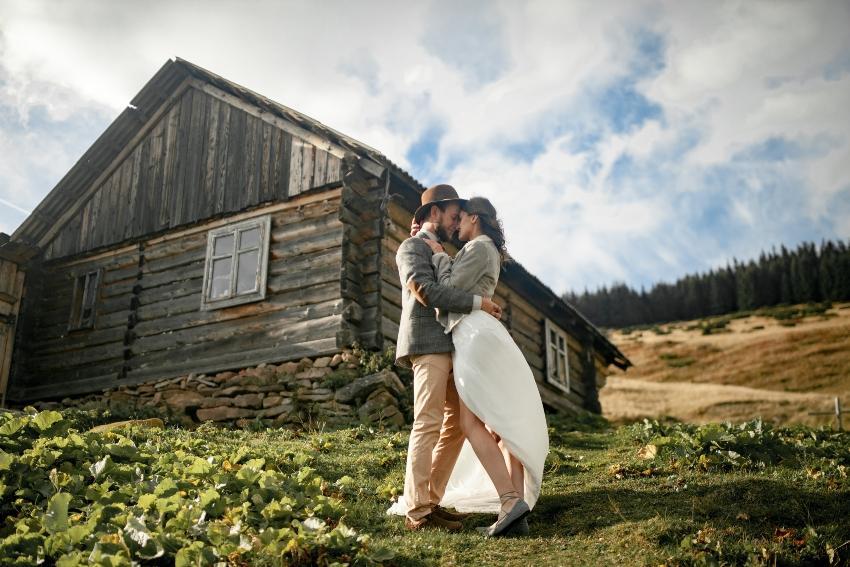 Junges Paar vor einer Berghütte - Romantische Hüttenhochzeit