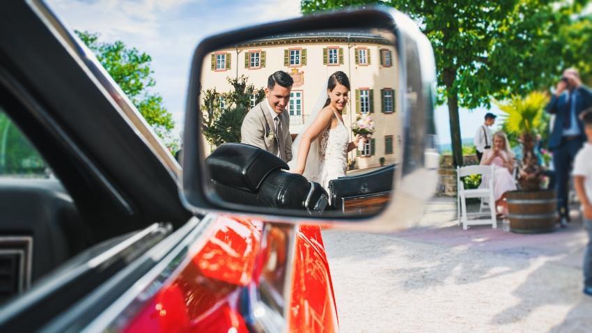 Junges Brautpaar im Rückspiegel eines Autos - ein Weddingplaner hilft bei der Organisation