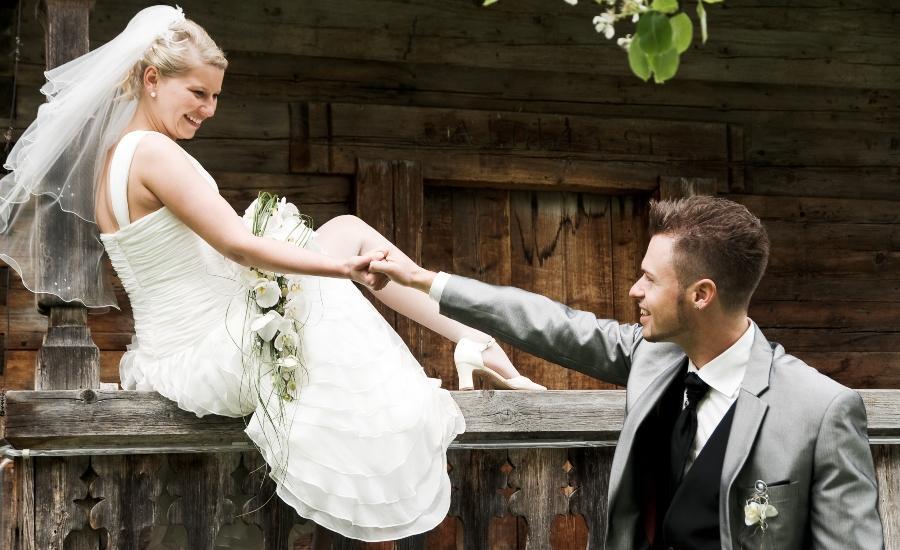 Junges Brautpaar vor einer Holzhütte - Romantische Hüttenhochzeit
