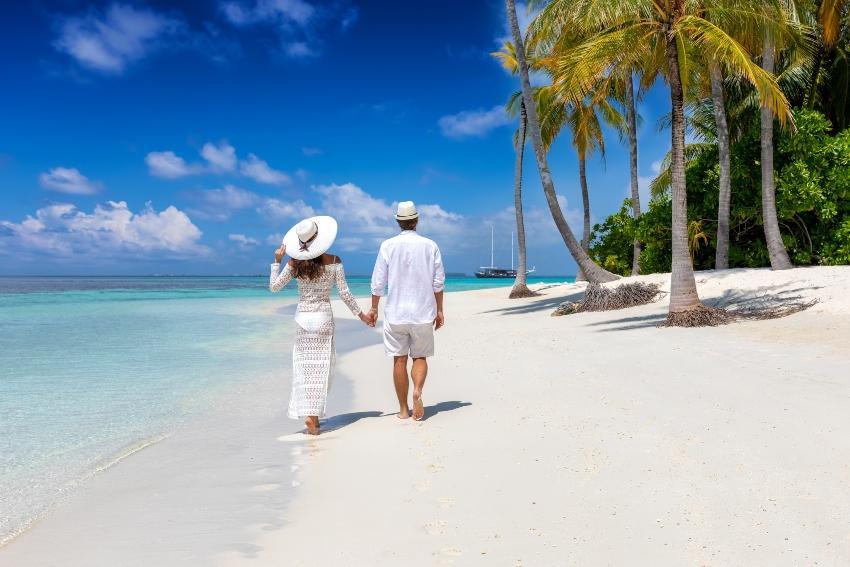 Pärchen läuft am Traumstand - perfekte Gelegenheit für einen Heiratsantrag auf den Malediven