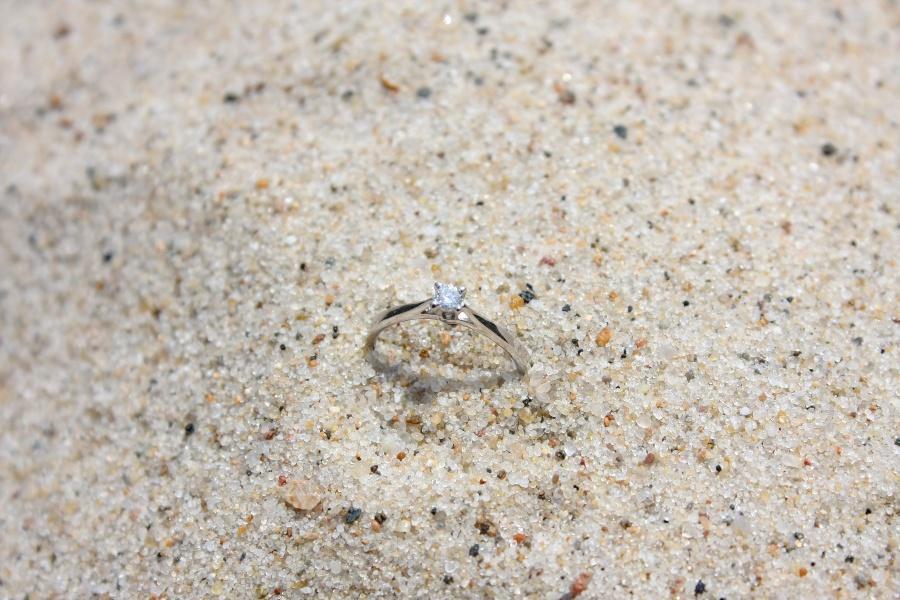 Verlobungsring liegt im hellen Sand am Strand - Ring verloren im Urlaub