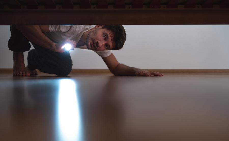 Junger Mann sucht mit Taschenlampe unter dem Bett - Ring verloren