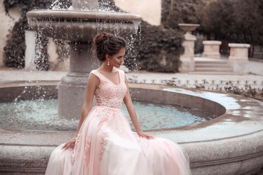 Schöne Braut sitzt mit rosafarbenem Hochzeitskleid auf einem Brunnen